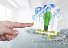Hand touching a Home with green energy lightbulb. Digital composite of Hand touching a Home with green energy lightbulb royalty free stock photos