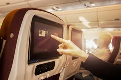 Hand touching LCD at the entertainment screen in a plane. During flight time Stock Photography
