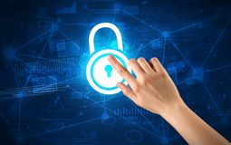 Hand touching lock. Female hand touching blue lock with charts and graphs in the background royalty free stock image
