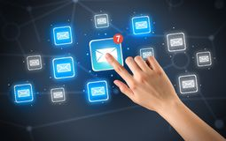Hand touching mail icon. Female hand touching unread mail icon with more envelope icons around it Royalty Free Stock Image