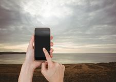 Hand Touching Mobile phone with evening sky landscape Royalty Free Stock Photo