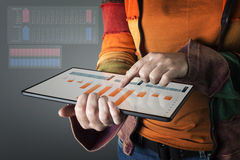Hand touching modern tablet with financial graph. Stock Photos