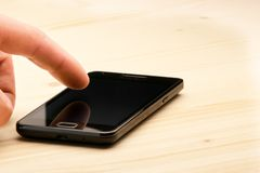 Hand touching screen of black smartphone Royalty Free Stock Photo