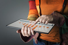 Hand touching screen modern tablet with financial graph. Stock Photo