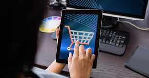 Hand touching shopping cart icon on tablet PC. Digital composite of Hand touching shopping cart icon on tablet PC Royalty Free Stock Photography