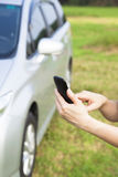 Hand touching the smart phone before  car Stock Image