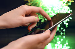 Hand Touching Smart Phone On Green Background Royalty Free Stock Photography