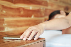 Hand touching smartphone on wooden table and woman on the bed Royalty Free Stock Photography