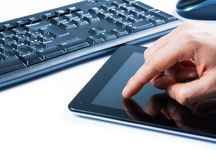 Hand touching tablet near keyboard, concept of new technology. Hand touching tablet near keyboard on white table, concept of new technology Stock Photos