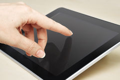 Hand touching tablet pc Stock Image