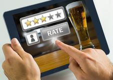 Hand touching tablet with Rate button and review stars in bar. Digital composite of Hand touching tablet with Rate button and review stars in bar Royalty Free Stock Photos