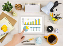 Hand touching tablet screen with chart over office desk background Royalty Free Stock Photo