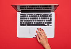 Hand touching touchpad on the silver laptop Royalty Free Stock Photography