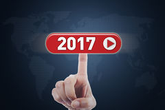 Hand touching virtual button with 2017. Picture of hand touching a virtual button with numbers 2017 and world map background on the futuristic screen Royalty Free Stock Images