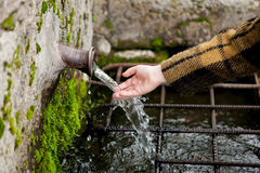 Hand touching water from a natural fountain Royalty Free Stock Photos