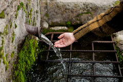 Hand touching water from a natural fountain Stock Photography