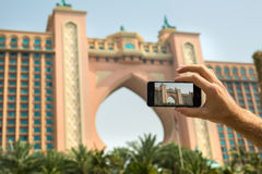 Hand tourist takes a picture of the hotel Atlantis Royalty Free Stock Image