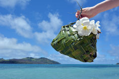 Hand of a tourist woman carry a Fijian basket made out of coconu. T tree leaves decorated with white plumeria flowers against blue lagoon and Island in Fiji Stock Photography