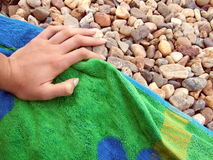 Hand on towel. A closeup of a manicured hand on a beach towel that has been placed on a pebbly beach royalty free stock photography