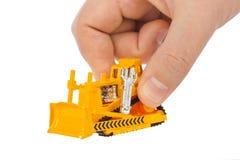 Hand with toy bulldozer. Isolated on white background Royalty Free Stock Image