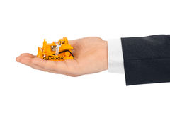 Hand with toy bulldozer. Isolated on white background Stock Photos