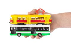 Hand with toy bus and tram. Isolated on white background royalty free stock photos