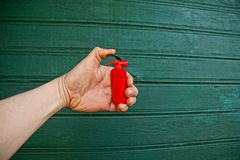 Hand with toy red fire extinguisher Royalty Free Stock Images