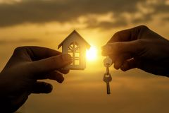 Hand transfers the key and the hand holds a house. royalty free stock images