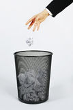 Hand and trashcan. Hand throwing a piece of paper into. Little motion blur on the paper Stock Image
