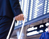 Hand of traveling businessman with baggage in front of airport timetable Royalty Free Stock Images