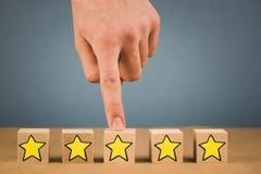 Hand trifft eine Wahl und wählt einen der Sterne, auf einem blauen Hintergrund stockfotografie