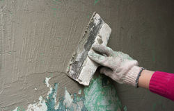 Hand with a trowel plaster wall royalty free stock image