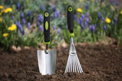 Hand trowel and a rake in garden soil Stock Images