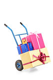 A hand truck with many gifts on it Stock Photos