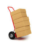 Hand truck with packages. Red hand truck with three cardboard boxes on it ready for delivery Royalty Free Stock Photos