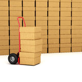 Hand truck with packages. Red hand truck with three cardboard boxes on it ready for delivery Royalty Free Stock Image