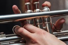 Hand of the Trumpeter on the buttons of trumpet. Hand of the Trumpeter on the buttons of the trumpet Stock Images