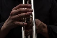 Hand of the Trumpeter on the buttons of trumpet. Hand of the Trumpeter on the buttons of the trumpet. Low key Royalty Free Stock Photo