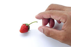 Hand try to pick a fresh strawberry Stock Photos