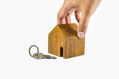 Hand try to pick up wodden house model with key Royalty Free Stock Photo