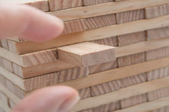 hand try to take off piece of wooden brick of constru Stock Images