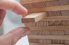 Hand try to take off piece of wooden brick of construction game. Closeup of hand try to take off piece of wooden brick of construction game royalty free stock photography