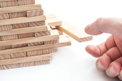 Hand try to take off piece of wooden brick of construction game. Closeup of hand try to take off piece of wooden brick of construction game royalty free stock photo