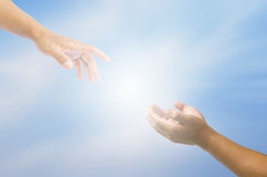 Hand trying to catch up on a background of sky and light - for help. Stock Image