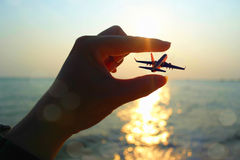 Hand Trying to Hold Plane. Hand trying to hold a flying plane with sunset as background at beach Royalty Free Stock Photography