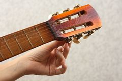 Hand tuning acoustic guitar Stock Photo