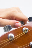 Hand tuning a guitar from headstock. Royalty Free Stock Photography