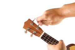 Hand Tuning Ukulele On White Royalty Free Stock Image
