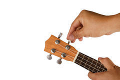 Hand tuning ukulele on white Royalty Free Stock Photo