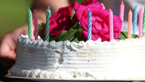 Hand turn cake with candle and flower. Hand turn white creamy delicious cake decorated three red roses on the top stock video footage